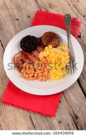 irish breakfast with black pudding, white pudding, baked beans and scrambled eggs on a white plate
