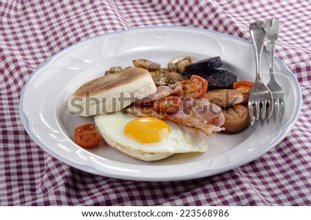 irish breakfast with muffin, black pudding, white pudding, fried egg, grilled cherry tomato and bacon