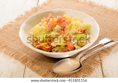 irish colcannon, made with mashed potato, cabbage, grilled bacon and crushes peppercorn in a bowl, with spoon - stock photo