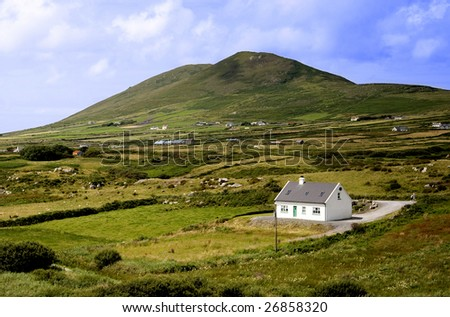 Irish country in the mountains, view on little white house. - stock photo