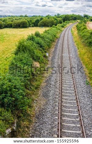 Irish country side with vanishing train tracks - stock photo