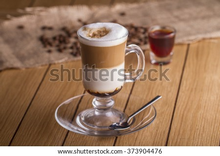 Irish cream coffee decorated with coffee beans on the table - stock photo