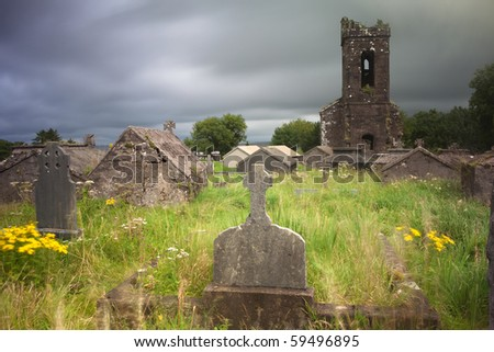 Irish graveyard at Dingle peninsula old ruins of church long exposure gives moody feel caused by blurry vegetation and clouds - stock photo