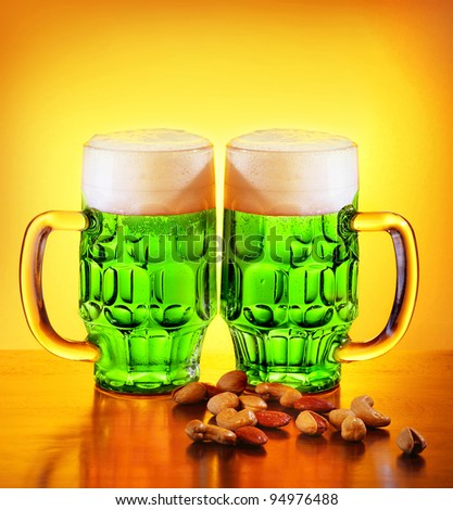 Irish green beer, traditional alcohol for st.Patrick's day holiday celebration, lucky clover beverage, two glasses with nuts, food and drink still life - stock photo