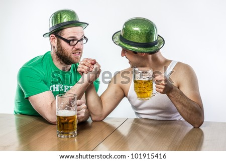 Irish Men arm wrestling in green hats on St. Patty's Day with mugs of frothy beer at local tavern, in white tank top and shirt - stock photo