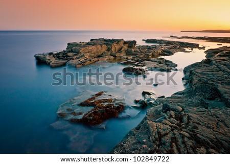 Irish Rocky shore at sunset using  long exposure. - stock photo
