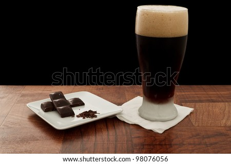 irish stout served in a chilled glass on a bar top isolated on black paired with chocolate