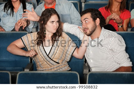 Irked woman gestures to punch man in theater - stock photo