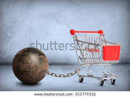 Iron ball with chain and empty shopping cart, closeup - stock photo