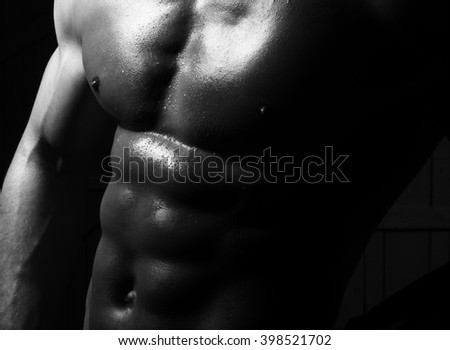 Iron cool sensual beautiful muscular awesome male torso with strong breast biceps pectoral and six-pack muscles closeup studio black and white on dark background