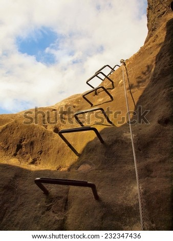 Iron cramps in rock, tourist ladder. Iron twisted rope fixed in block by screws snap hooks. The rope end anchored into sandstone rock. Climbers way. - stock photo
