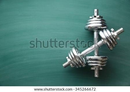 iron dumbbell on green chalkboard - stock photo