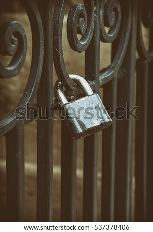 Iron lock on the black forged fence, close up, vintage toning