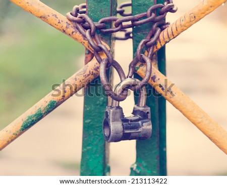 iron lock with a chain on the fence, retro effect - stock photo