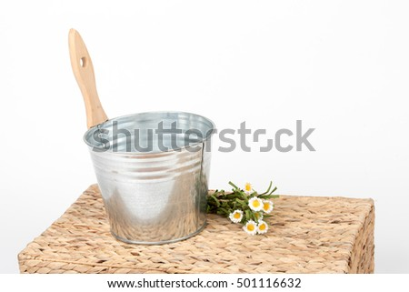 Iron/metal sauna bucket with wooden handle, on braided box/ pad/  table isolated on a white background. Detail of sauna pail/ container with artificial flowers, isolated on white background.