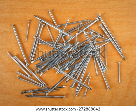 iron nails on a wooden background - stock photo