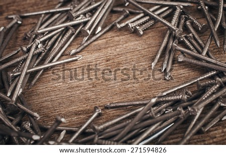 iron nails on wooden background wits copyspace - stock photo
