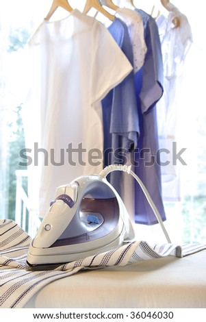 Iron on ironing board with clothes hanging in background - stock photo