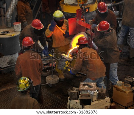 Iron Pour - Filling the Cup - crowd of workers gather around to fill the cup from the bull ladle - stock photo