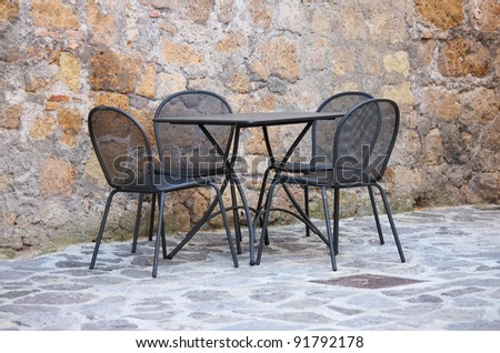 Iron table and chairs on outdoors cafe in Mediterranean Europe - stock photo