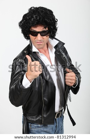 Ironic rocker in a wig and leather jacket - stock photo