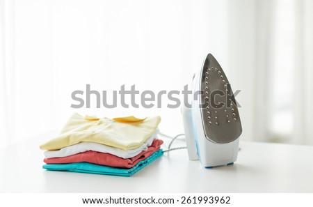 ironing, clothes, housework and objects concept - close up of iron and clothes on table at home - stock photo