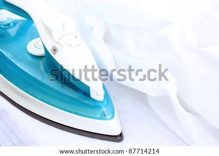 ironing white clothing with electric iron - stock photo