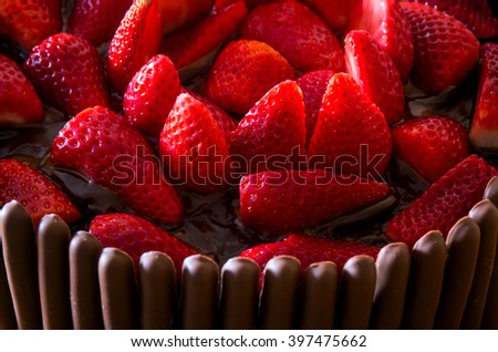 Irresistible frash chocolate and strawberry cake over yellow background
