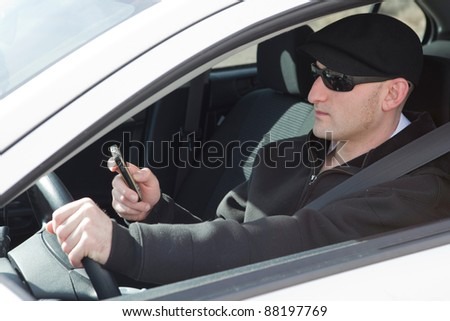 Irresponsible man behind the wheel and texting on his cell phone - stock photo