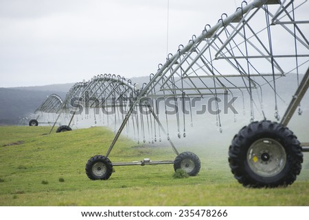 Irrigation by pivot sprinkler and spray system on green grass field or meadow on rural agricultural farm land, copy space. - stock photo