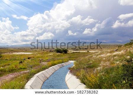 Irrigation canal in the valley between the mountains - stock photo