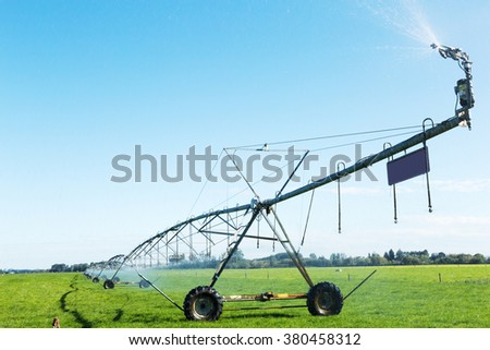 irrigation machine working in modern meadow in blue sky - stock photo