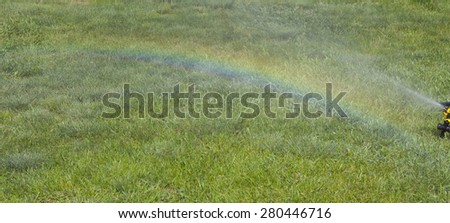 Irrigation system of the lawn at the sunshine produces a rainbow over green grass. - stock photo