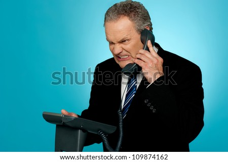 Irritated businessman communicating on phone. Anger expression on his face - stock photo
