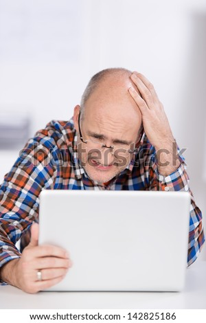 Irritated businessman looking at laptop while sitting in office - stock photo