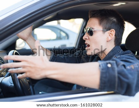 Irritated driver. Irritated young male driving a car - stock photo