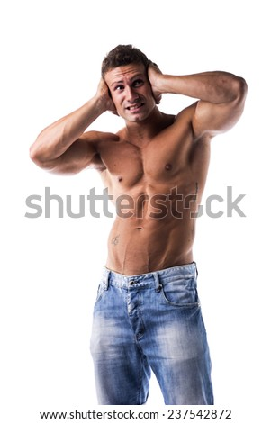 Irritated, frustrated, stressed shirtless muscular young man covering his ears, too much noise - stock photo