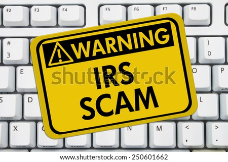 IRS Scam Warning Sign,  A yellow sign with the words IRS Scam on a keyboard - stock photo
