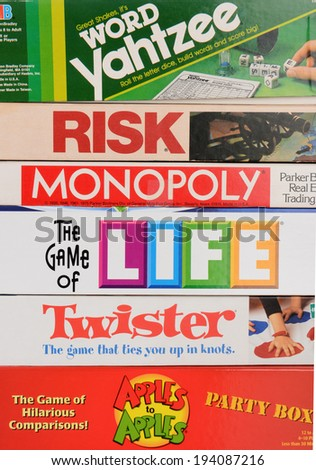 IRVINE, CA - MAY 19, 2014: A stack of Family Board Games. Classic games from Parker Brothers and Milton Baradley, including Monopoly, Twister, Life, Risk, Yahtzee and Apples to Apples.  - stock photo