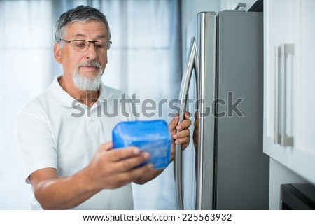 Is this still fine? Senior man in his kitchen by the fridge, looking at the expiry date of a product she took from her fridge - - stock photo