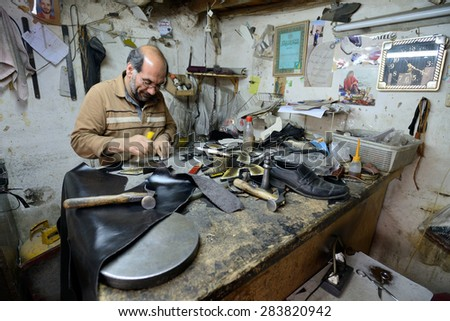 ISFAHAN - APRIL 18: Unknown man making shoes in a market (Isfahan Bazaar) in Isfahan, Iran on April 18, 2015. Bazaar is the most important tourist attraction in Isfahan, Iran.