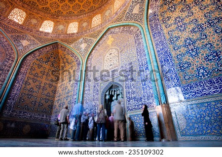 ISFAHAN, IRAN - OCT 14: Group of tourists view beautiful interior design of patterned Lotfollah Mosque on October 14 2014. Naqsh-e Jahan Square constructed in 1598. It is UNESCO's World Heritage Sites - stock photo