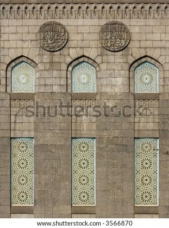 islamic architecture: wall with three  windows and symbols - stock photo