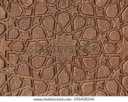 Islamic flowers and stars motif pattern, carved on the surface of an old wooden door. - stock photo