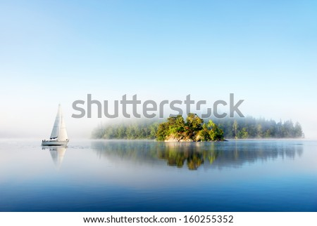 Island and yacht reflected in clear blue Scandinavian lake on foggy sunny morning - stock photo