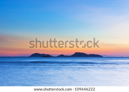 Island at sunset over the ocean - stock photo