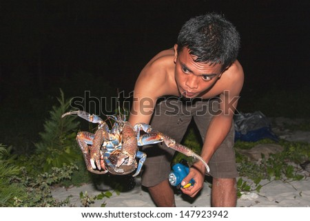 ISLAND OF NEW GUINEA, NATIONAL PARK SENDERVASIH, JANUARY 11: Catcher shows crabs caught coconut crab, the National Park Serdenvasih, New Guinea, Indonesia, January 11, 2009 - stock photo