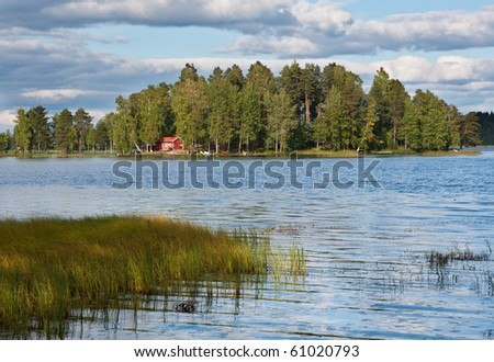 Island on lake in Finland with red summer cottage - stock photo