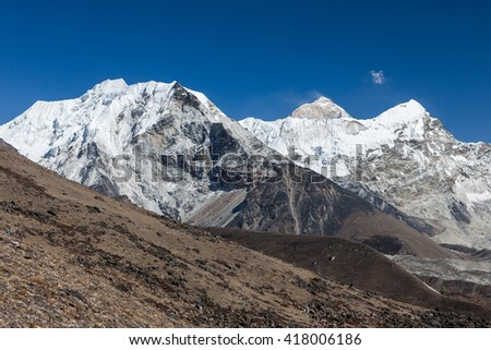Island Peak or Imja Tse and Makalu view on the way to Everest Base Camp in Sagarmatha National Park, Himalayas, Nepal. Mountain summits in snow under the blue sky. Summits of Himalayan mountains. - stock photo