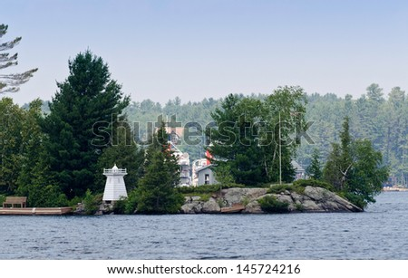 Island with a toy lighthouse - stock photo